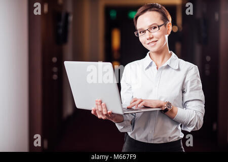Businesswoman with Glasses Holding Laptop Computer - Stock Photo