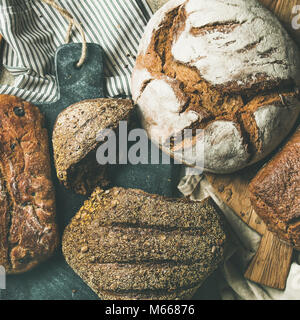 Flat-lay of various bread loaves on grey background, square crop - Stock Photo