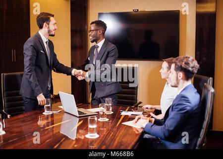 Business people shaking hands, finishing up a meeting. - Stock Photo