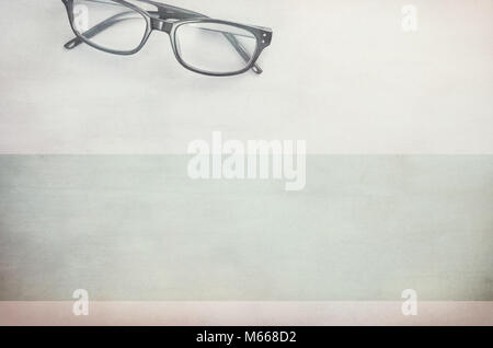 pair of framed eyeglasses on a light textured surface - directly above - Stock Photo
