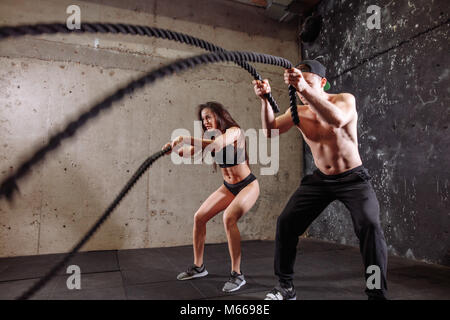 Woman and man couple training together doing battling rope workout - Stock Photo