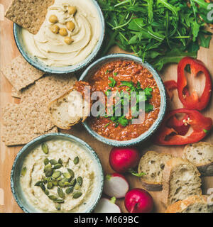 Flat-lay of Vegetarian dips hummus, babaganush, muhammara, square crop - Stock Photo