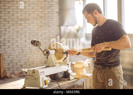 man working at small wood lathe, an artisan carves piece of wood - Stock Photo