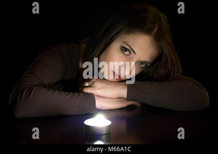 Portrait of young beautiful woman with burning candle - Stock Photo