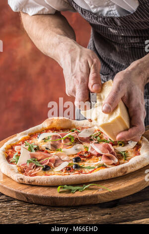 Pizza and Chef. Chef in the restaurant prepares a pizza and decorates it with parmesan cheese. - Stock Photo