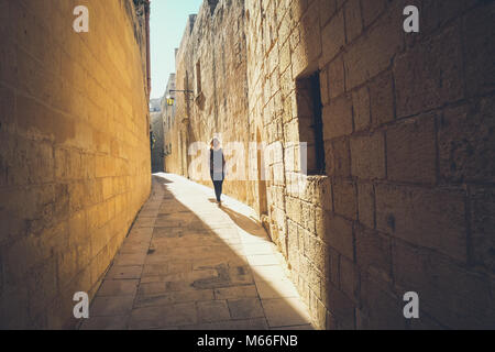 Narrow streets of the old Mdina. Tourist walking. Typical architecture in Malta - Stock Photo