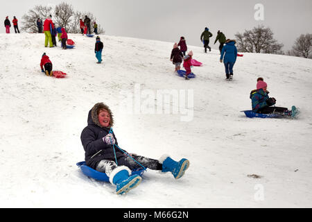 Skipton, North Yorkshire / UK - February 28th 2018: A girl slides down a snow covered hill on a sledge after snow - Stock Photo