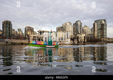 Downtown Vancouver, British Columbia, Canada - January 28, 2017 - A small taxi ferry boat is riding in False Creek - Stock Photo