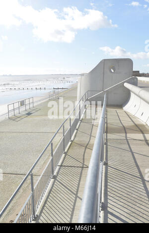 The huge brutalist concrete sea defences at Dymchurch in Kent. The sky is dramatic and the sun is bright casting - Stock Photo