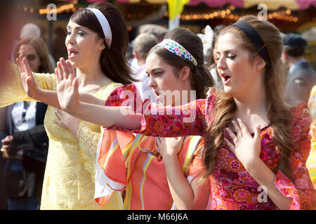 Three young women in brightly coloured 1960's style dresses looking happy attending the Goodwood revival meeting - Stock Photo