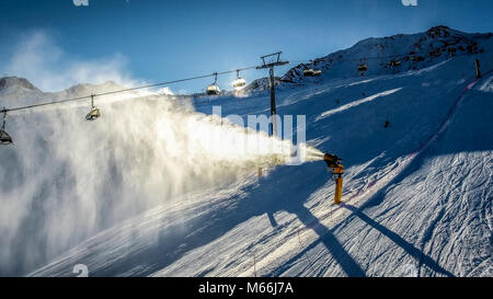 Skiers and chairlifts at sunset in Alpine ski resort . HDR image. - Stock Photo
