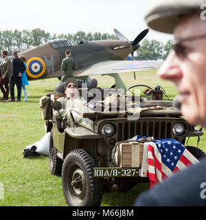Willis jeep with American flag on airfield with RAF spitfire plane in the background on location at the Goodwood - Stock Photo