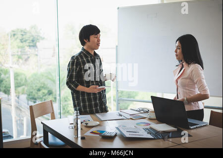 Asian businesswoman discussing and brainstorm with young freelance man in meeting room. Business company co-operate - Stock Photo