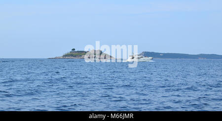 Tourist boat sailing on a sea passing an island on its way - Stock Photo