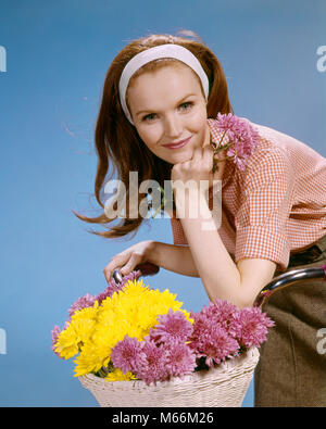 1960s SMILING REDHEAD YOUNG WOMAN RIDING BICYCLE WITH BASKET OF FLOWERS LOOKING AT CAMERA - kf5477 HAR001 HARS FEMALES - Stock Photo
