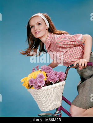 1960s REDHEAD WOMAN RIDING BICYCLE WITH BASKET FULL OF AUTUMN FLOWERS - kf5479 HAR001 HARS YOUNG ADULT BALANCE RIDE - Stock Photo
