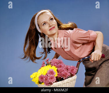 1960s REDHEAD WOMAN RIDING BICYCLE WITH BASKET FULL OF AUTUMN FLOWERS - kf5480 HAR001 HARS YOUNG ADULT BALANCE RIDE - Stock Photo