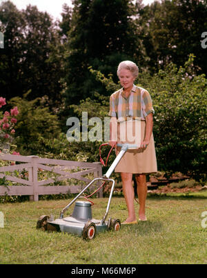 1960s SENIOR WOMAN PUSHING ELECTRIC LAWN MOWER CUTTING GRASS - kg3628 HAR001 HARS ELECTRICAL STYLE PLAN MOWING CAUCASIAN - Stock Photo