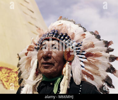 1960s NATIVE AMERICAN INDIAN MAN CHIEF GULL WEARING FEATHER BONNET MORLEY STONEY SIOUX FIRST NATIONS RESERVATION - Stock Photo