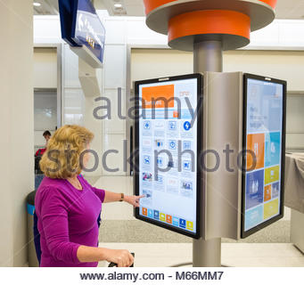 Woman using large interactive electronic display to find information on dining and services available inside Terminal - Stock Photo
