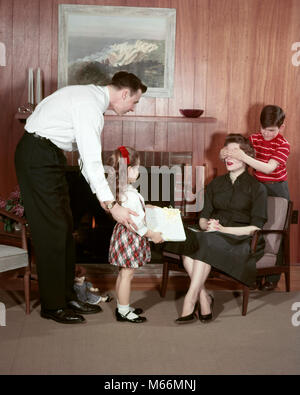 1950s FAMILY IN LIVING ROOM SURPRISING MOTHER WITH GIFT FATHER DAUGHTER HOLD GIFT SON COVERS MOMS EYES - km187 HAR001 - Stock Photo