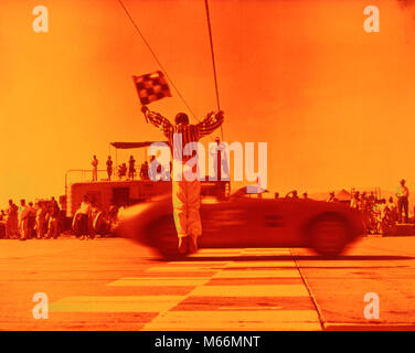 1970s MAN WAVING CHECKERED FLAG AT FINISH LINE END OF SPORTS CAR RACE ORANGE FILTER - km3108 HAR001 HARS AUTOMOBILE - Stock Photo