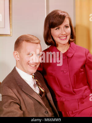 1960s PORTRAIT SMILING YOUNG COUPLE MAN IN BUSINESS SUIT WOMAN WEARING RED DRESS - kp1117 HAR001 HARS FEMALES MARRIED - Stock Photo