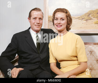 1960s HAPPY COUPLE SITTING ON SOFA MAN WEARING BUSINESS SUIT TIE WOMAN IN A YELLOW DRESS LOOKING AT CAMERA SMILING - Stock Photo