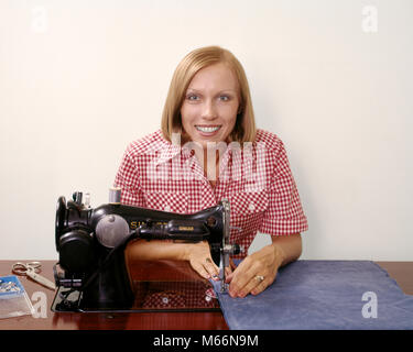 1970s SMILING BLOND WOMAN HOUSEWIFE LOOKING AT CAMERA OPERATING ANTIQUE BLACK SINGER SEWING MACHINE - ks13624 HAR001 - Stock Photo