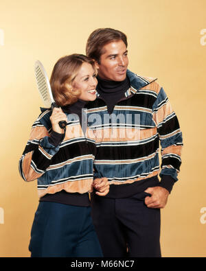 1970s SMILING COUPLE MAN WOMAN HOLDING SQUASH RACKET WEARING MATCHING STRIPED VELOUR PULLOVER SWEATERS FASHION SPORTSWEAR - Stock Photo