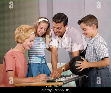 1960s HAPPY FAMILY IN BOWLING ALLEY LOOKING AT SCORE SHEETS BOY HOLDING BALL - ks1847 HAR001 HARS BOWL TOGETHER - Stock Photo