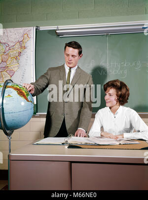 1960s 2 STUDENTS IN CLASSROOM TEEN BOY STAND BY GLOBE GIRL SEATED AT DESK MAP CHALKBOARD HIGH SCHOOL - ks2012 HAR001 - Stock Photo
