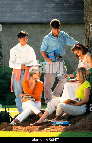 1990s FIVE COLLEGE STUDENTS WITH TEXTBOOKS ON CAMPUS TALKING UNDER A TREE - ks31723 DEG002 HARS CLOTHING NOSTALGIC - Stock Photo