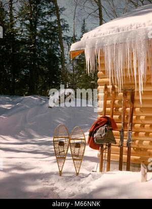 1970s SNOW SNOWSHOES TWO PAIR SKIS JACKET BACKPACK LEANING AGAINST WALL LOG CABIN SKI LODGE MOUNTAIN RETREAT - kw5864 - Stock Photo