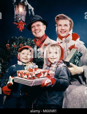 1950s FAMILY MAN WOMAN TWO KIDS HOLDING CHRISTMAS PRESENTS SMILING STANDING BENEATH LANTERN - kx2215 HAR001 HARS - Stock Photo