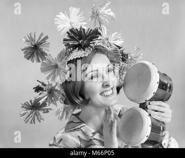 1960s SMILING WOMAN WAEARING GOOFY STRAW HAT PLAYING BONGO DRUMS - m7415 HAR001 HARS LADIES DRUMS CARIBBEAN INDOORS - Stock Photo