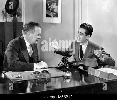 1930s 1940s TWO MEN SEATED AT DESK YOUNGER MAN TALKING GESTURING ARMS UP OLDER MAN LISTENS - o1828 HAR001 HARS INDOORS - Stock Photo