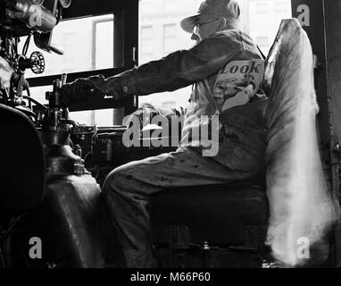 1940s ABOARD THE HIAWATHA RAILROAD TRAIN ENGINEER IN CAB OF LOCOMOTIVE WITH HAND ON THROTTLE COPY LOOK MAGAZINE - Stock Photo