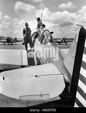 1940s 2 ARMY PILOTS STANDING FUSELAGE OF SLIDING COCKPIT SINGLE ENGINE AIRPLANE WING US ARMY AIR CORPS RANDOLPH - Stock Photo