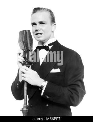 1920s 1930s SMILING MAN RADIO SINGER ENTERTAINER CROONER IN TUXEDO SINGING INTO MICROPHONE - r10906 HAR001 HARS - Stock Photo