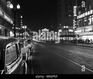 1930s 1940s NIGHT NEON SIGNS AND PARKED CARS ALONG 4TH AVENUE SEATTLE WASHINGTON USA - r12877 HAR001 HARS WA - Stock Photo