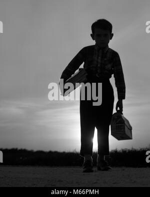 1960s 1970s SILHOUETTE OF ANONYMOUS YOUNG BOY HOLDING BOOKS AND LUNCH PAIL IN RISING MORNING SUN ON WAY TO SCHOOL - Stock Photo