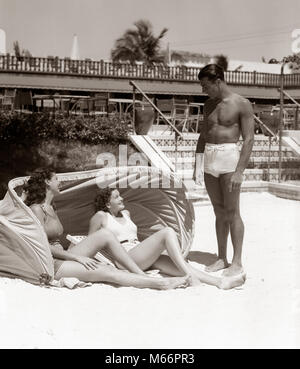 1930s 1940s MAN BATHING TRUNKS TALKING TO TWO WOMEN LAYING UNDER HOTEL CANVAS SUN SCREEN TROPICAL SAND MIAMI BEACH - Stock Photo