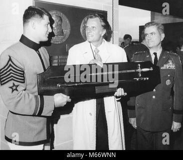 Evangelist Billy Graham (center) receives a ceremonial sword from Cadet Robert Van Antwerp (left) during ceremonies - Stock Photo
