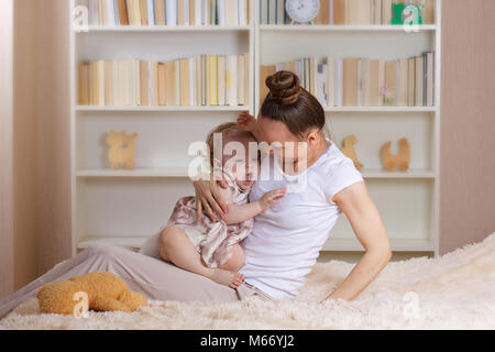 Young mother with her one year old daughter. Closeup - Stock Photo