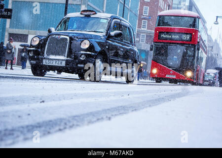 London, United Kingdom 1st March 2018 The famous black cabs and red buses travel atop snow-capped roads of Central - Stock Photo