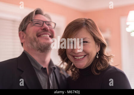 happy smiling couple laughing and having fun at friends party - Stock Photo