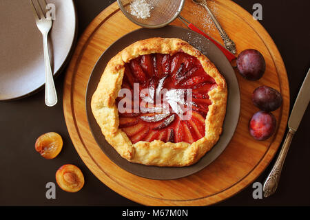 Healthy homemade wholegrain fruit galette with plums sugar powder . - Stock Photo