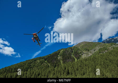 Helicopter taking off in a forest at Argentiere, a small alpine village with several hiking routes in summer. Near - Stock Photo