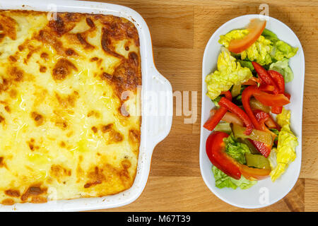 Shepherd's pie or cottage pie is a meat pie with a crust of mashed potato. The defining ingredients are minced meat, - Stock Photo